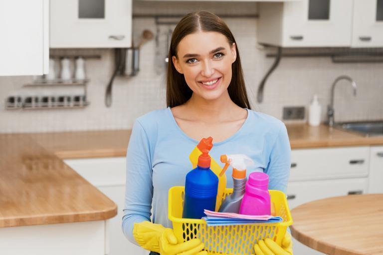 Kobieta ze środkami czystości wkuchnii